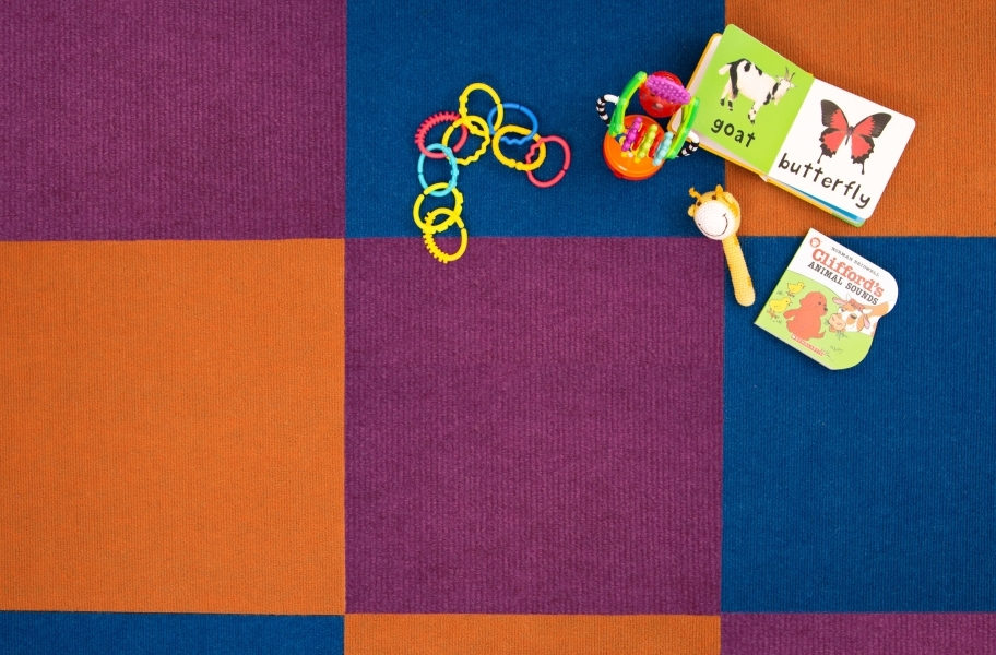 close up view of carpet tiles with children's toys in a playroom