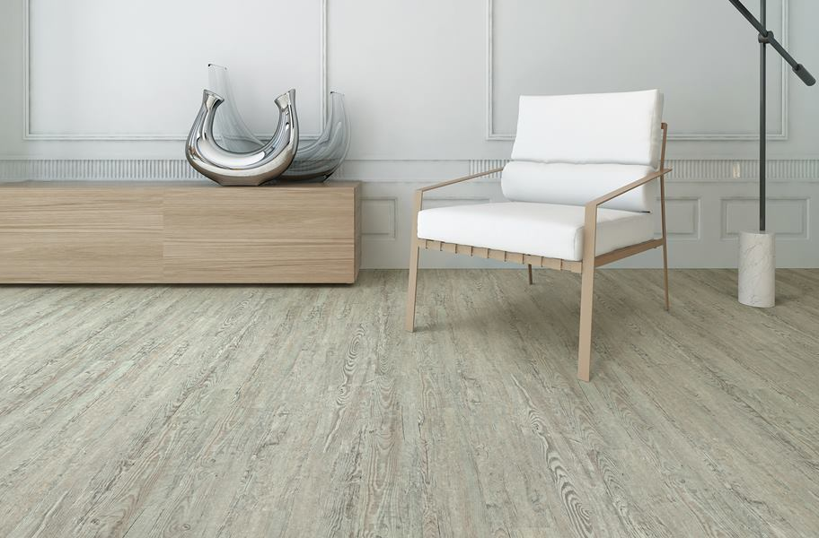 SPC vs. WPC: Gray wood-look SPC vinyl flooring in a living room setting.