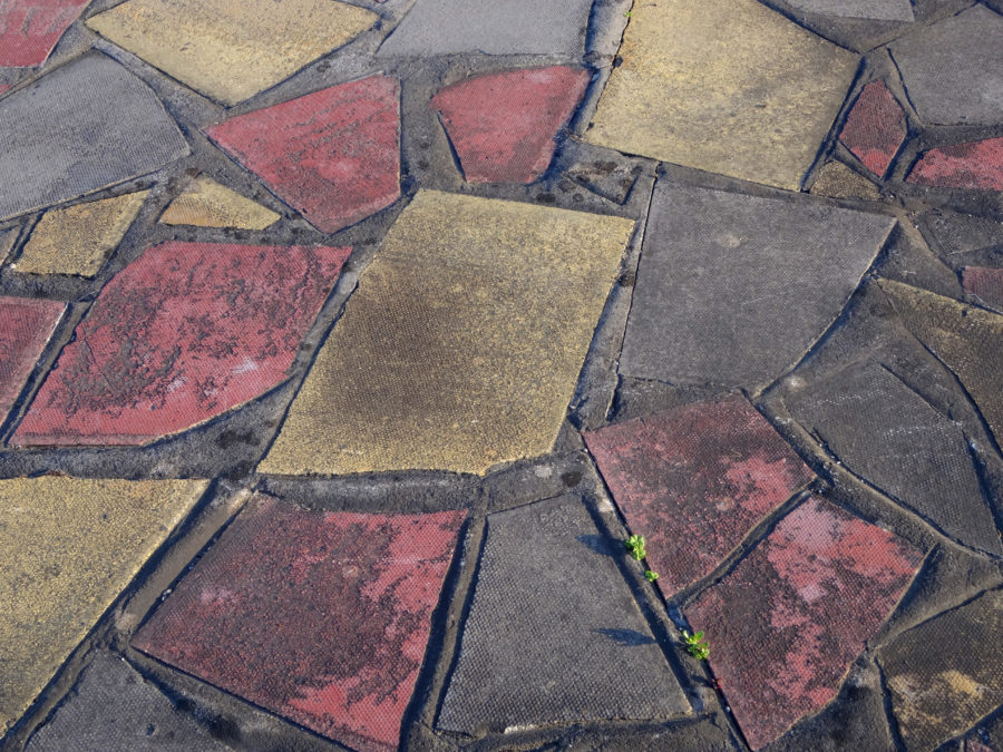 Photo showing a rather retro-style crazy paving patio, which is made up from a mixture of different coloured, broken paving slabs - yellow, pink / red and grey. These concrete slabs are arranged to form a random mosaic pattern, rather like a giant jigsaw puzzle.