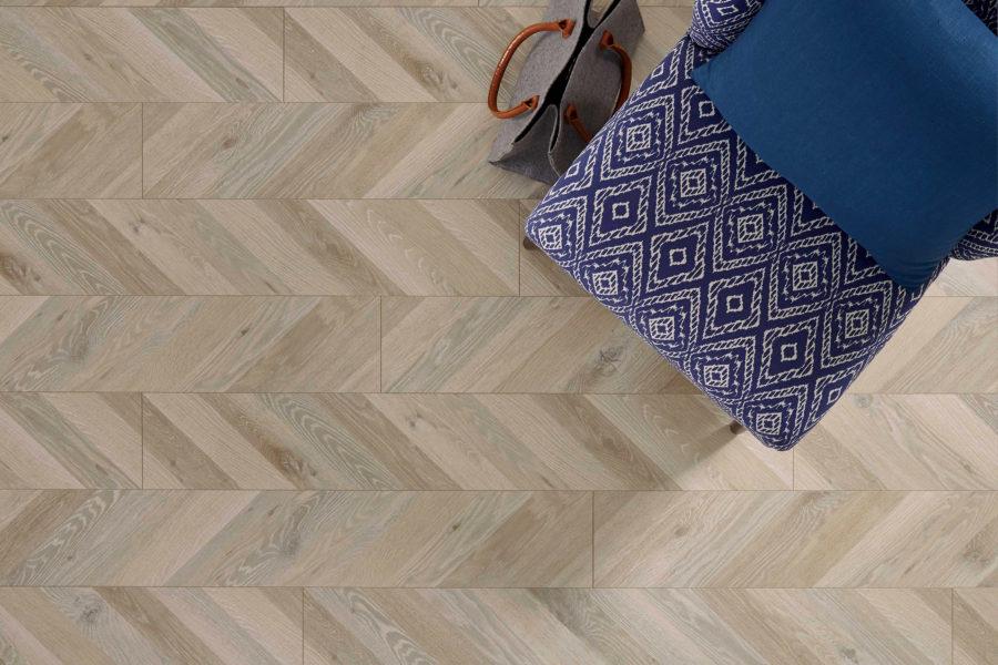 FlooringInc Mannington Palace Waterproof Laminate Flooring in herringbone pattern under a chair and purse