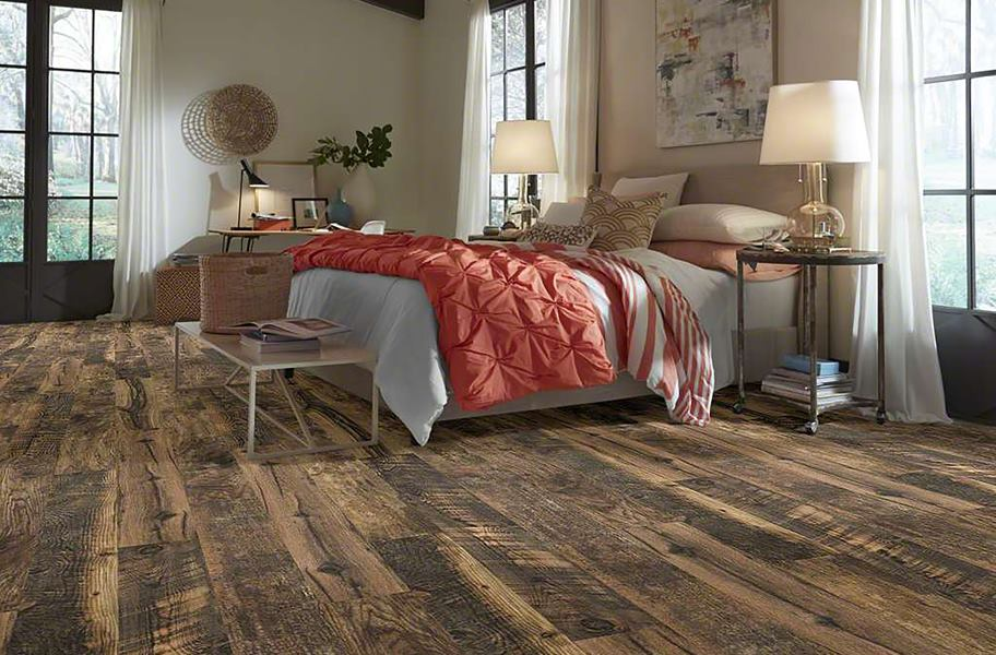 12mm Woodhaven Water-Resistant Laminate in bedroom with bed, coral blankets, and night stands