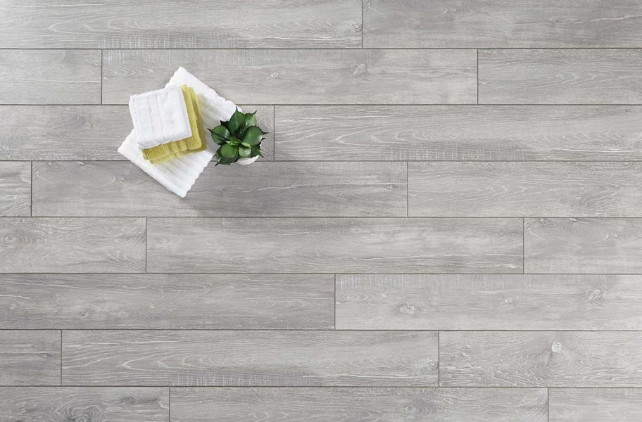 gray laminate flooring flat lay with hand towels, washcloths and plant.