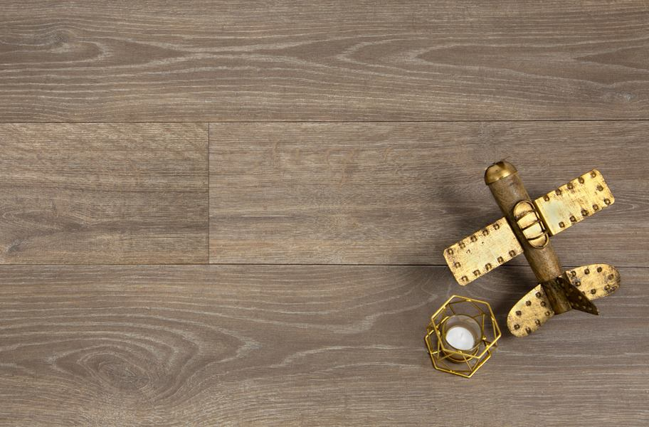 flat lay of brown wooden laminate planks and candle and antique toy plane