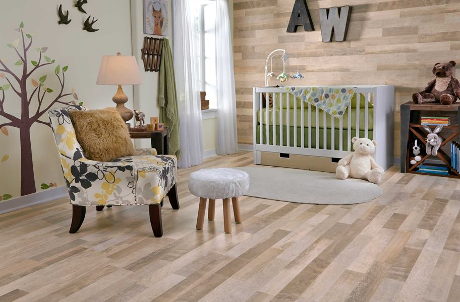 nursery scene of light laminate flooring, a chair, stool, and a crib with toys