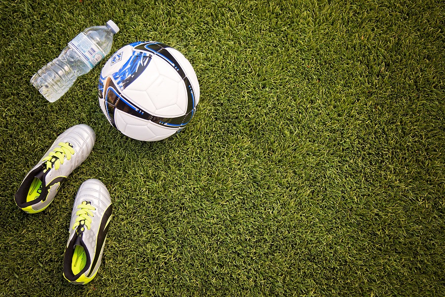 soccer ball and cleats on artificial field turf