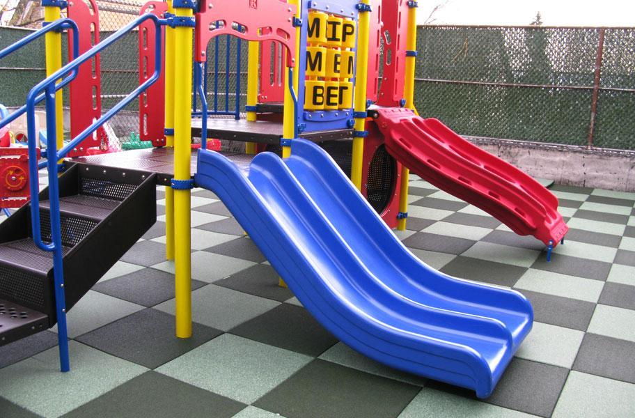 blue slide on checkered playground tiles