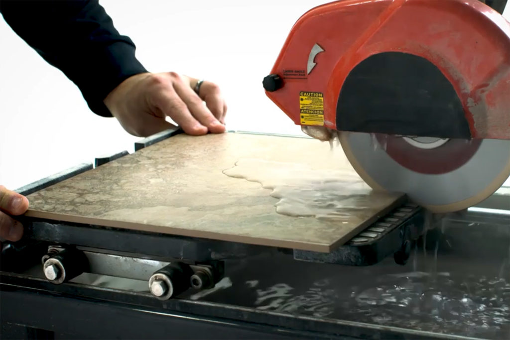 Cutting a ceramic floor tile with a wet saw