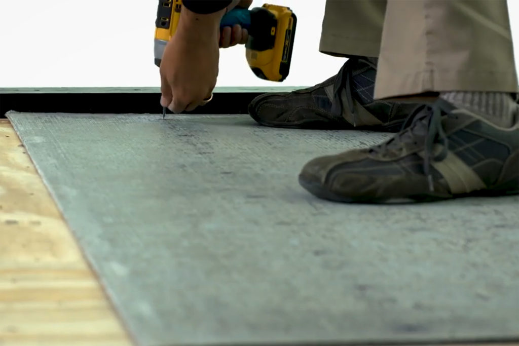 Securing a cement backer board to a plywood subfloor for tile installation prep.