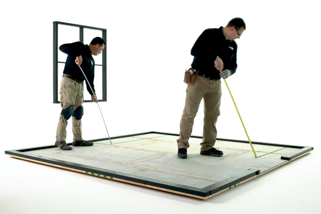 Installation professionals measuring a room for tile