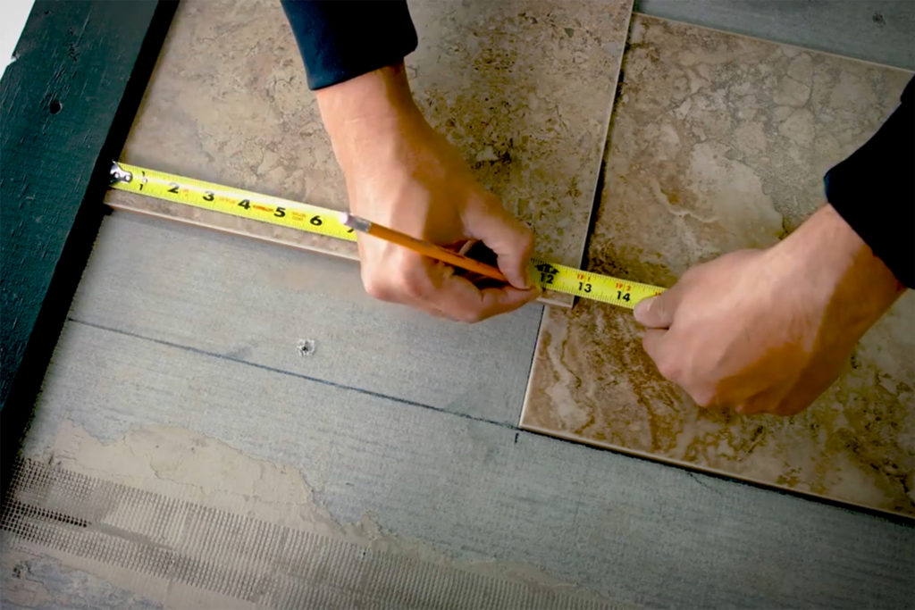 Measuring a ceramic floor tile while laying floor tile