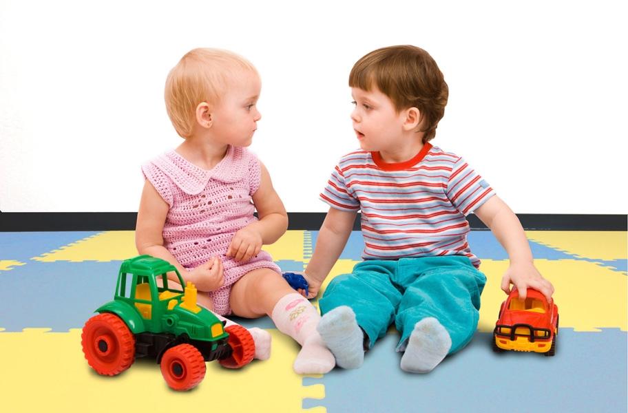 Babies playing on EVA foam floor tiles in a playroom setting