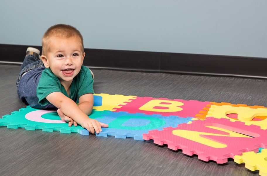 Toddler playing with Alphabet foam tiles