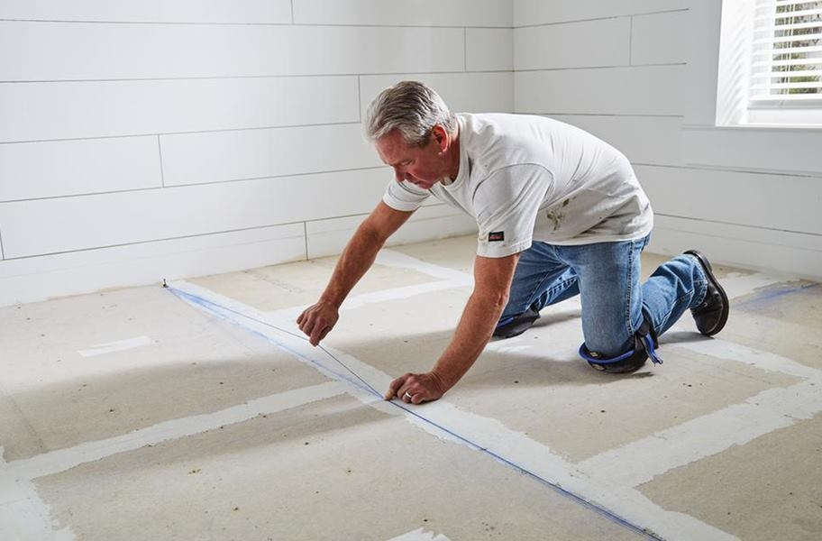 Man prepping the subfloor for installation wearing Stabilizer Knee Pads