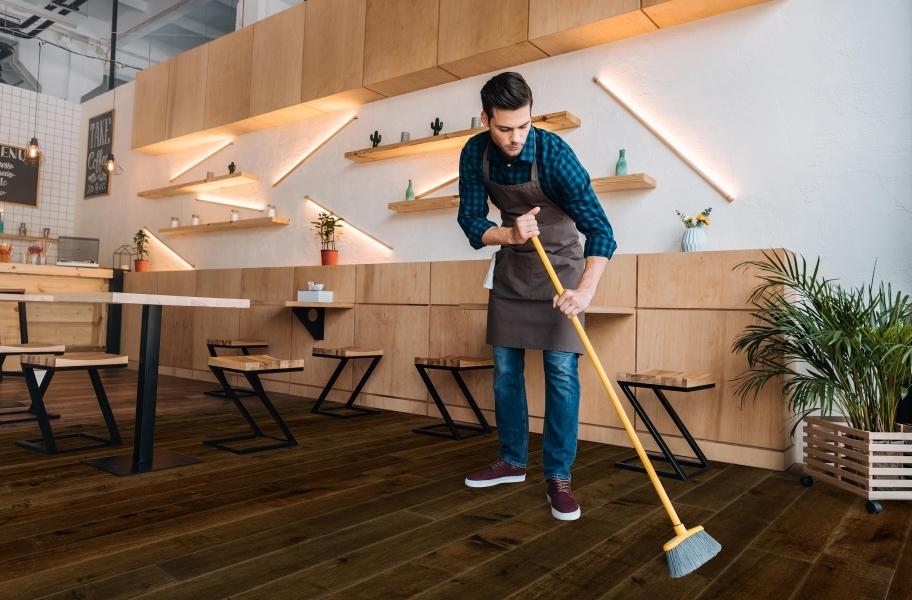 Sweep Regularly: Man sweeping Rio Grande Water Resist Oak Engineered Wood